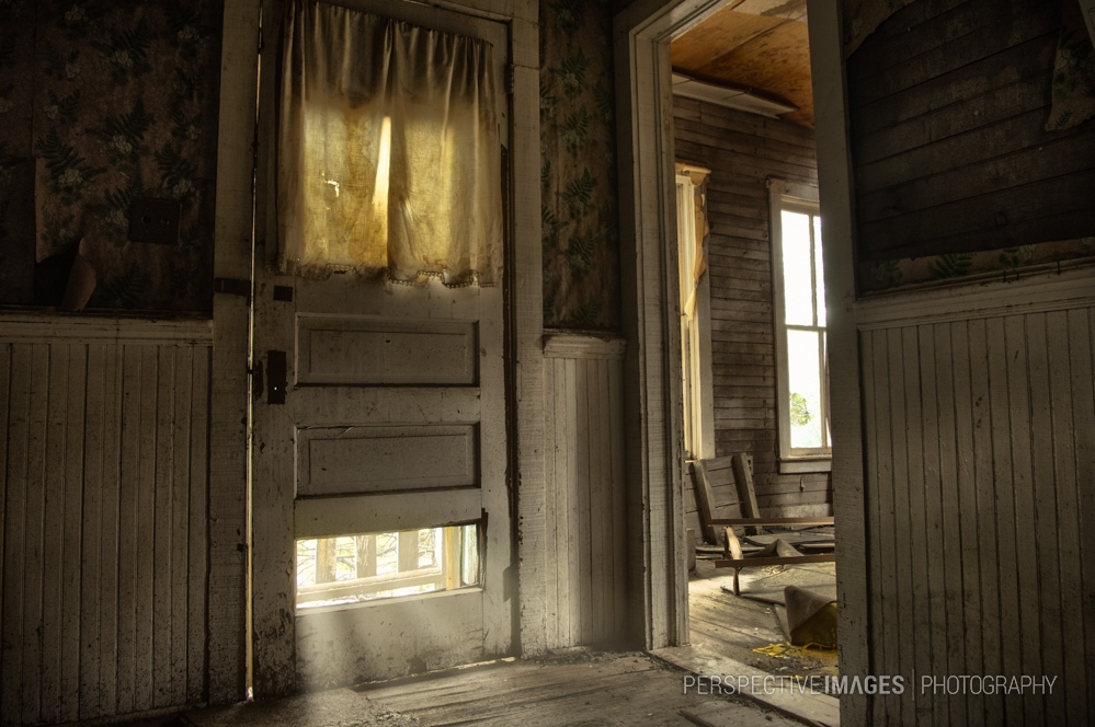 Who's That Knocking? - Light creeps under the front door of an abandoned house in a former gold mining town.