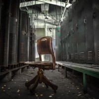 Pull up a Chair - Office chair sits in an abandoned locker room.