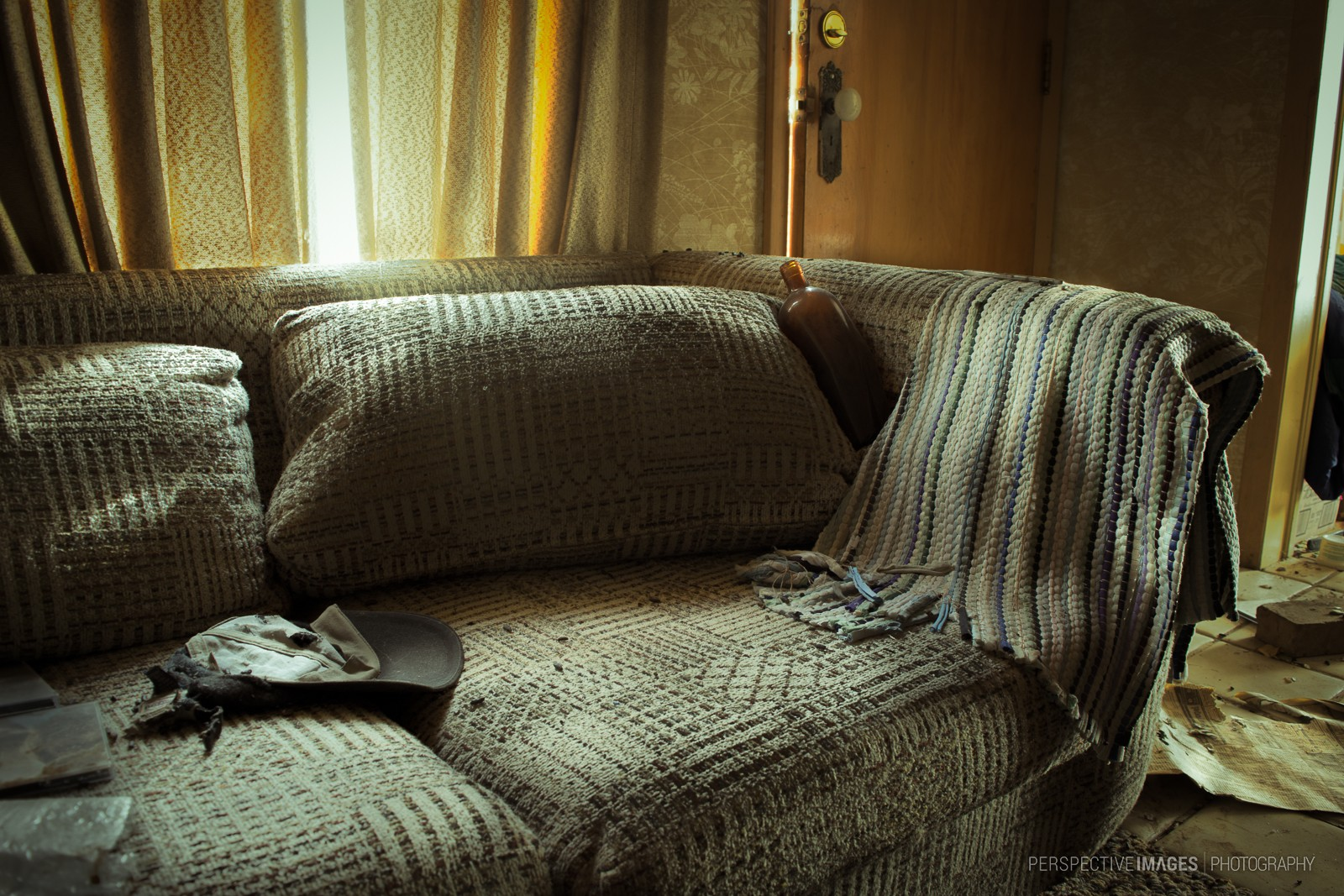 Sit Down, Relax Awhile - An empty bottle propped in the corner of a sofa at an abandoned house.