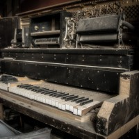 Lost Melody - The school house piano gathers dust as packaging builds up around it.