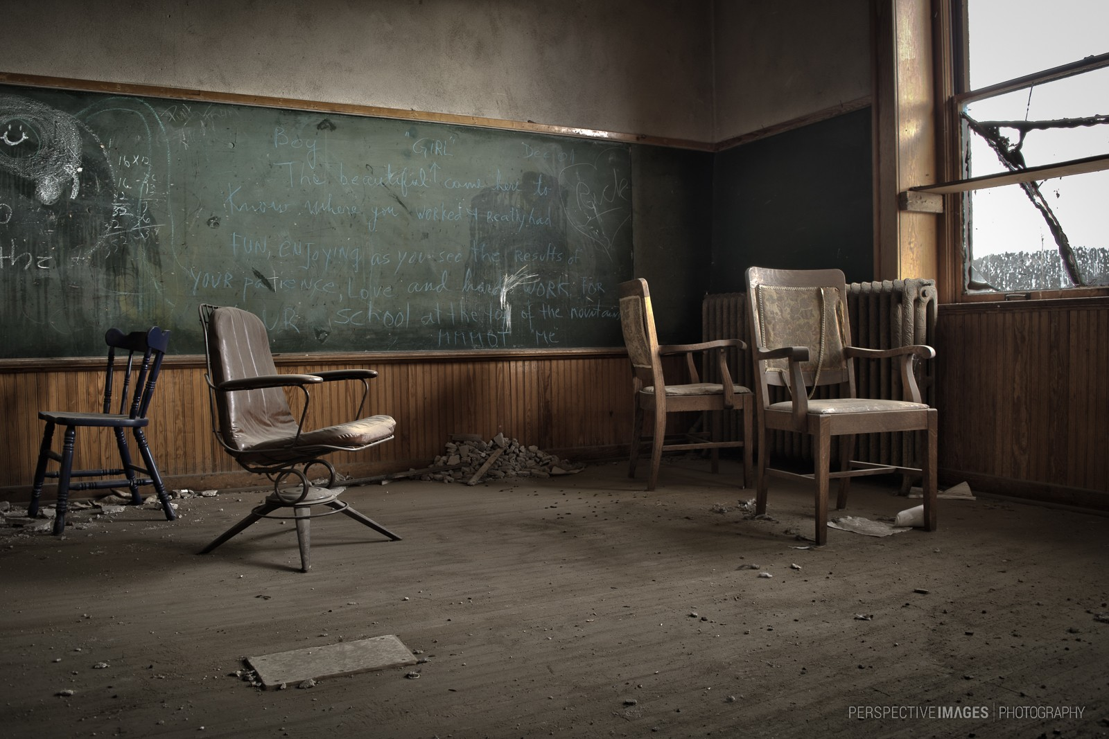 School House Blues - Teachers chairs sit covered in dust at an abandoned school house.