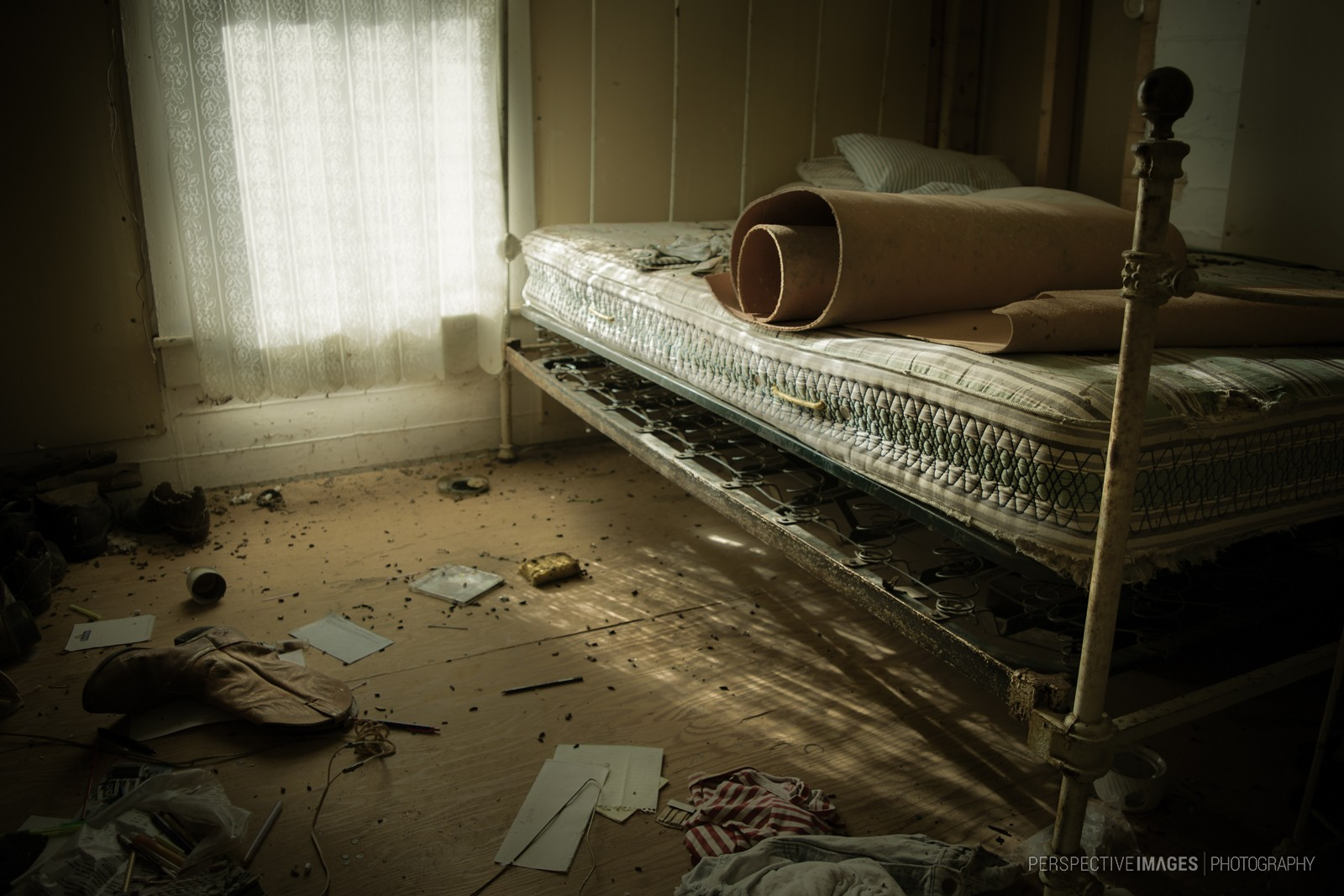 Don't Let the Bed Bugs Bite - Light filters through curtains in an abandoned bedroom.