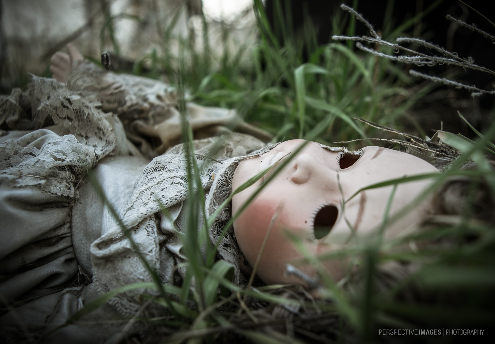 I See Straight Through You - A lifeless, abandoned doll, discarded in the grass.